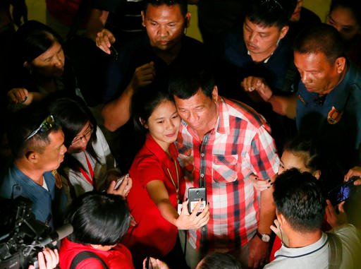 Front-running presidential candidate Mayor Rodrigo Duterte poses for a selfie with a supporter following his second news conference after voting in a polling precinct.