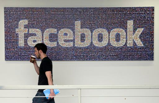In this March 15, 2013, file photo, a Facebook employee walks past a sign at Facebook headquarters in Menlo Park, Calif.
