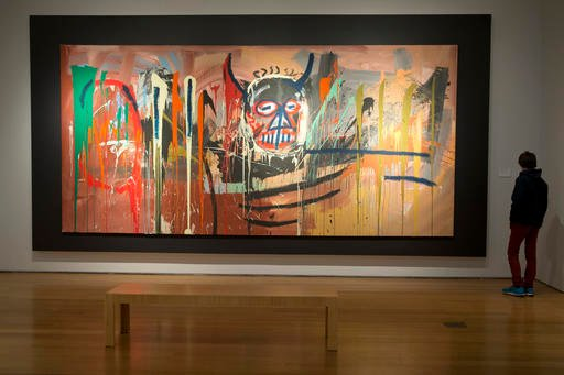 """In this April 29, 2016, file photo, a visitor inspects """"Untitled"""" by Jean-Michel Basquiat on display during the press preview of """"Bound to Fail"""" at Christie's auction house in New York."""