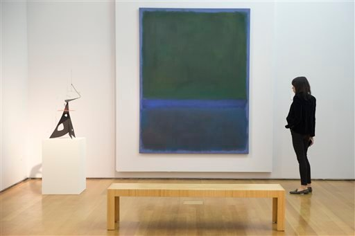 """In this Friday, April 29, 2016 file photo, an employee inspects """"No. 17"""" (blue and green) by Mark Rothko, on display during the press preview of """"Bound to Fail"""" at Christie's auction house in New York."""
