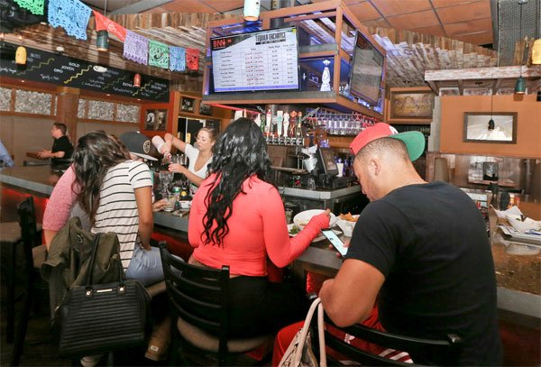 In this Thursday, May 5, 2016, photo, a bartender makes a drink at The Blind Burro, in San Diego, where the tequila prices can change every five minutes based on demand.