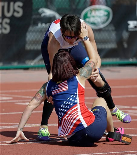 Marion Blot, standing, of France, winner of the women's 200 meter IT1 race, catches Sarah Rudder after she fell crossing the finish line at the Invictus Games, Tuesday, May 10, 2016, in Kissimmee, Fla. (AP Photo/John Raoux)