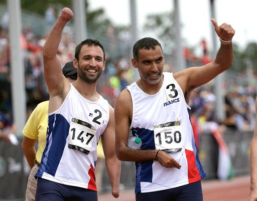 Jonathan Hamou, left, and teammate Djamel Mastouri, both of France, celebrate after finishing the men's 200 meter IT3 race at the Invictus Games, Tuesday, May 10, 2016, in Kissimmee, Fla. (AP Photo/John Raoux)