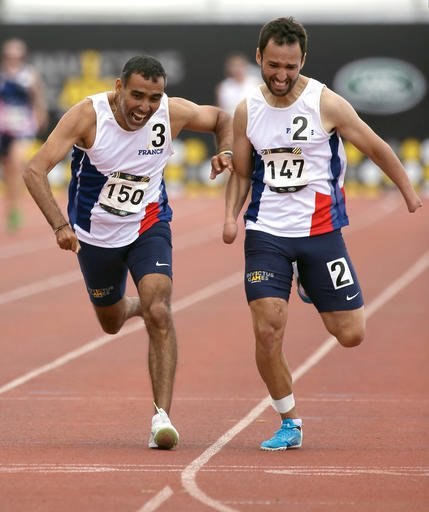 Djamel Mastouri, left, of France, stumbles inches before the finish line as he and teammate Jonathan Hamou race to win the men's 400 meter IT3 race during the Invictus Games, Tuesday, May 10, 2016, in Kissimmee, Fla. (AP Photo/John Raoux)