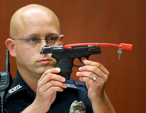 In this June 28, 2013, file photo, Sanford police officer Timothy Smith holds up the gun that was used to kill Trayvon Martin.