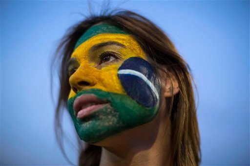 An anti-government demonstrator shows off her Brazilian flag motif face paint outside Congress in Brasilia, Brazil, Wednesday, May 11, 2016.