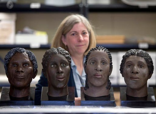 In this April 27, 2016 photo, Lisa Anderson, curator of bioarchaeology at the New York State Museum, poses in Albany, N.Y., with facial reconstructions of slaves found at an unmarked cemetery.