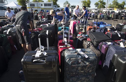 Baggage sits in the special events parking lot, Thursday, May 12, 2016, at Phoenix Sky Harbor International Airport. More than 3,000 checked bags missed their outbound flights in Phoenix because of a problem with a screening system at Sky Harbor Internati