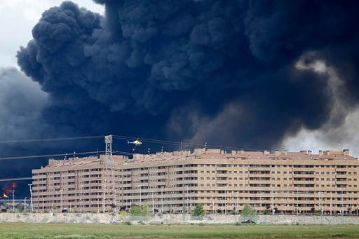A fire fighting helicopter flies billowing black smoke rising from behind large housing blocks in Sesena, central Spain, Friday, May 13, 2016.
