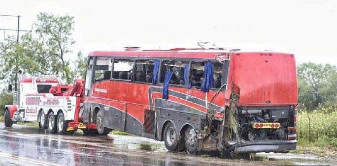A bus is seen being towed away after a deadly rollover crash in Webb County, Texas, Saturday, May 14, 2016.