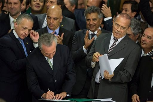 In this May 12, 2016, file photo, Brazil's acting President Michel Temer signs a document as he swears in his ministers, at Planalto presidential palace in Brasilia, Brazil, after the Senate voted to suspend President Dilma Rousseff pending an impeachment
