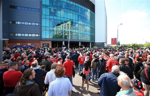 Spectators stand outside of Old Trafford stadium after today's final soccer match of the season between Manchester United and AFC Bournemouth was abandoned due to a suspect package being found inside the stadium. Sunday May 15, 2016. (Mike Egerton/PA via