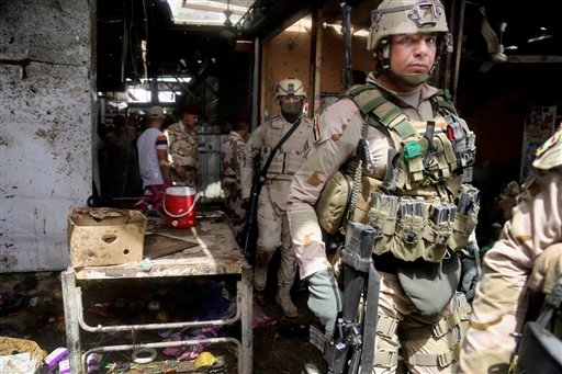 Security forces and citizens inspect the scene after a bomb explosion at an outdoor market in Baghdad's northern neighborhood of Shaab, Iraq, Tuesday, May 17, 2016. A bomb at an outdoor market in a Shiite-dominated Baghdad neighborhood on Tuesday killed m