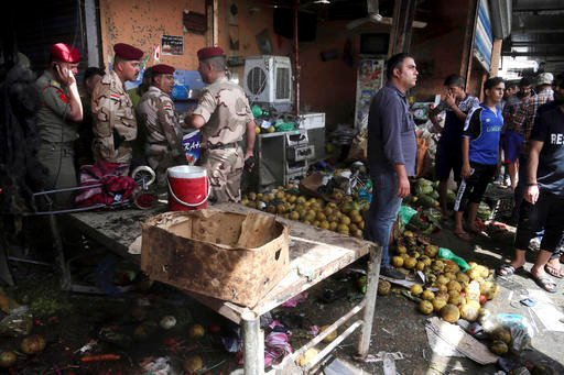 Security forces and citizens inspect the scene after a bomb explosion at an outdoor market in Baghdad's northern neighborhood of Shaab, Iraq, Tuesday, May 17, 2016. A bomb at an outdoor market in a Shiite-dominated Baghdad neighborhood on Tuesday, killing
