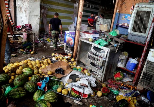 Citizens inspect the scene after a bomb explosion at outdoor market in Baghdad's northern neighborhood of Shaab, Iraq, Tuesday, May 17, 2016. A bomb at an outdoor market in a Shiite-dominated Baghdad neighborhood on Tuesday killed more than 30 people and