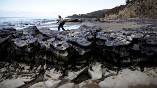 In this May 21, 2015, file photo, David Ledig, a national monument manager from the Bureau of Land Management, walks past rocks covered in oil at Refugio State Beach, north of Goleta, Calif. Plains All American Pipeline said in a statement Tuesday, May 17