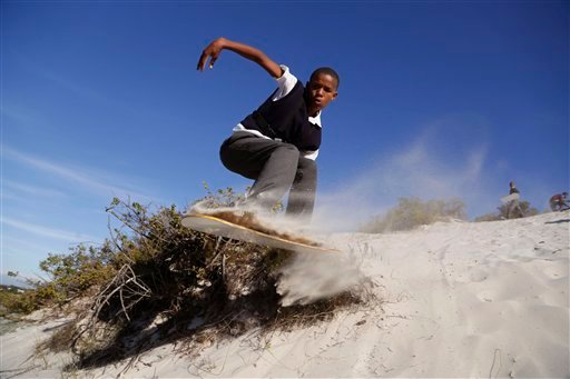 In this photo taken Friday, May 6, 2016, sandboarder Tyrese Hugo gets airborne at Atlantis area on the outskirts of Cape Town, South Africa.