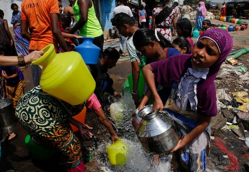 In this April 30, 2016 file photo, people collect water for non-drinking use as the same is pumped out from a construction site at a slum area in Mumbai, Maharashtra state, India. Earth's heat is stuck on high. Federal scientists said the globe shattered