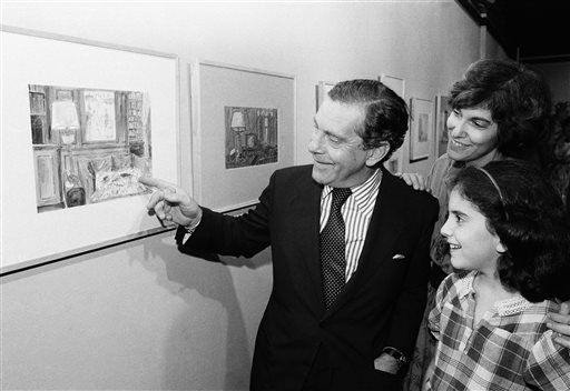 In this Sept. 22, 1980 file photo, Morley Safer points to one of his watercolors displayed at a New York restaurant as his wife Jane and daughter Sarah look on.