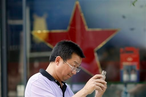 A man uses his mobile phone near a red star along a retail shop in Beijing Friday, May 20, 2016.