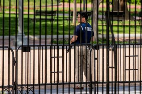 A security agent stands nearby the Northwest gate of the White House in Washington, Friday, May 20, 2016, after the White House is placed on lockdown for a shooting nearby. (AP Photo/Andrew Harnik)