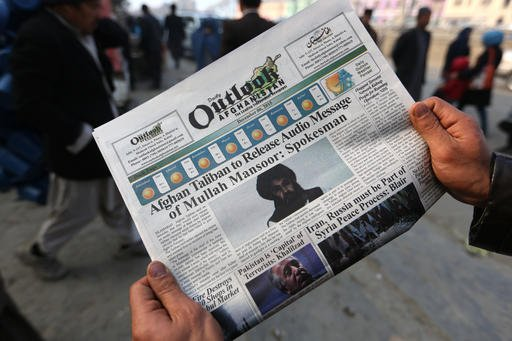 In this Dec. 6, 2015 file photo, an Afghan man reads a local newspaper with photos of the leader of the Afghan Taliban, Mullah Mansour, in Kabul, Afghanistan. The Pentagon has announced that the U.S. has conducted an airstrike targeting Taliban leader Mul