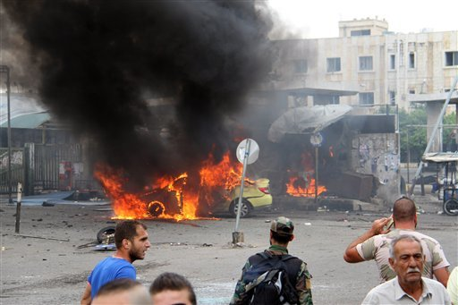 In this photo released by the Syrian official news agency SANA, Syrians gather in front of a burning car at the scene where suicide bombers blew themselves up, in the coastal town of Tartus, Syria, Monday, May 23, 2016. The Syrian TV said suicide bombers
