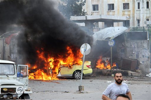 In this photo released by the Syrian official news agency SANA, Syrians gather in front of a burning car at the scene where suicide bombers blew themselves up, in the coastal town of Tartus, Syria, Monday, May 23, 2016. Syrian TV said suicide bombers blew