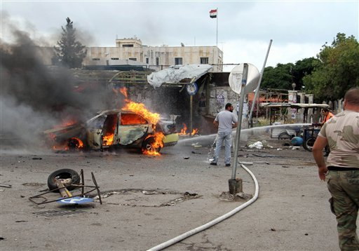 In this photo released by the Syrian official news agency SANA, a firefighter, right, extinguishes a burning car at the scene where suicide bombers blew themselves up, in the coastal towns of Tartus, Syria, Monday, May 23, 2016. Syrian TV said suicide bom