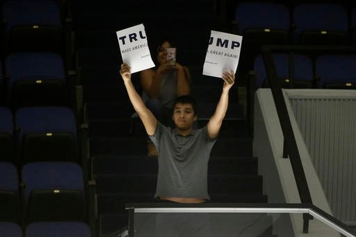 A protester holds up a sign ripped apart during a rally for Republican presidential candidate Donald Trump at the Anaheim Convention Center, Wednesday, May 25, 2016, in Anaheim, Calif.