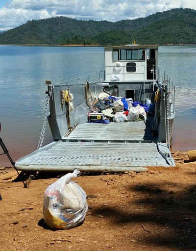 This Tuesday, May 24, 2016 photo provided by the U.S. Forest Service shows bags of trash on a boat after cleaning up a half-mile-wide swath of trash left behind by about 1,000 campers after an annual trip to Lake Shasta, Calif., by fraternity and sorority