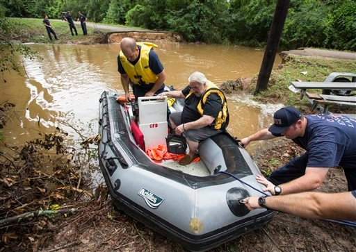Conroe firefighters evacuate Jim Treadway via boat after Treadway was stranded when Pecan Bend Road was washed out near the San Jacinto River on Friday, May 27, 2016, in Conroe, Texas. ( Brett Coomer/Houston Chronicle via AP