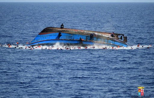 In this May 25, 2016 file photo made available by the Italian Navy, people try to swim away moments after their boat overturned off the Libyan coast. Over 700 migrants are feared dead in three Mediterranean Sea shipwrecks south of Italy in the last few da