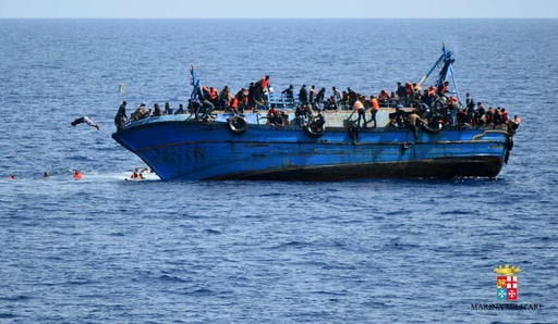 In this May 25, 2016 file photo made available by the Italian Navy, people try to jump in the water right before their boat overturns off the Libyan coast. Over 700 migrants are feared dead in three Mediterranean Sea shipwrecks south of Italy in the last