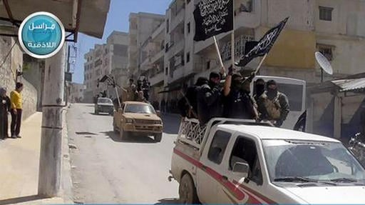 This file image posted on the Twitter page of Syria's al-Qaida-linked Nusra Front on April 25, 2015, which is consistent with AP reporting, shows Nusra Front fighters standing on their vehicles and waving their group's flags as they tour the streets of Ji