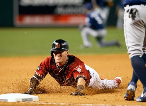 Arizona Diamondbacks Chris Herrmann dives into third base after hitting a triple against the San Diego Padres in the seventh inning during a baseball game, Sunday, May 29, 2016, in Phoenix. (AP Photo/Rick Scuteri)