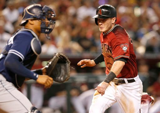 Arizona Diamondbacks Nick Ahmed, right, scores in front of San Diego Padres catcher Christian Bethancourt on a sacrifice bunt by Archie Bradley in the second inning during a baseball game, Sunday, May 29, 2016, in Phoenix. (AP Photo/Rick Scuteri)