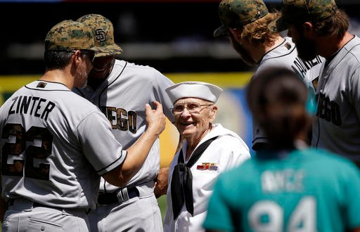 World War II veteran Burke Waldron wears a U.S. Navy uniform as he greets members of the San Diego Padres before a baseball game against the Seattle Mariners on Monday, May 30, 2016, in Seattle. Waldron also threw out the ceremonial first pitch, as part o