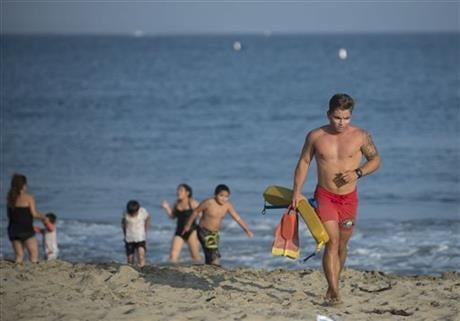 Thousands of Memorial Day beachgoers were kept out of the water Monday as lifeguards searched miles of popular Southern California shoreline for a shark they believe attacked a swimmer the day before. (Cindy Yamanaka/The Orange County Register via AP