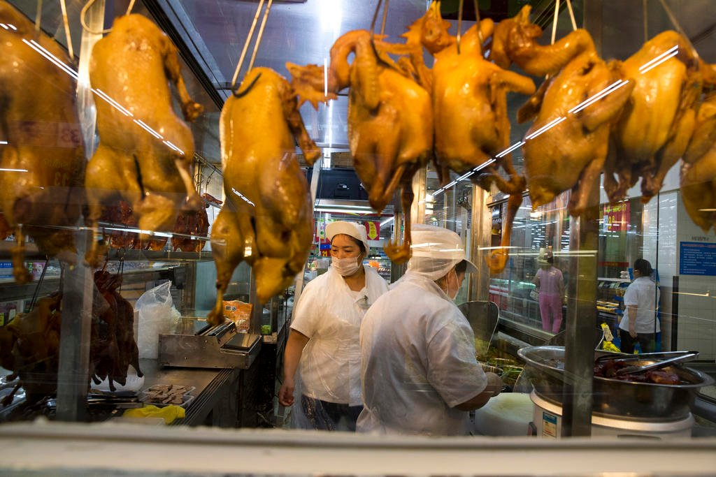 In this Wednesday, Nov. 11, 2015, photo, a worker prepares cooked ducks for sale at a Wal-Mart in Shenzhen, in southern China's Guangdong province.