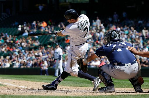 Seattle Mariners' Seth Smith hits a solo home run as San Diego Padres catcher Christian Bethancourt looks on in the fifth inning of a baseball game, Tuesday, May 31, 2016, in Seattle. It was Smith's second home run of the game. (AP Photo/Ted S. Warren)