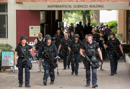 Los Angeles Police officers walk by the Mathematical Sciences Building on the UCLA campus after a fatal shooting at the University of California, Los Angeles, Wednesday, June 1, 2016, in Los Angeles.