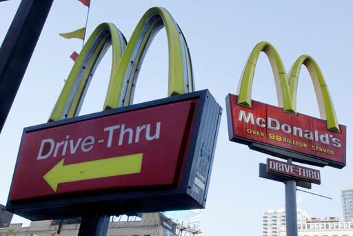 Dec. 20, 2010, file photo, McDonald's signs sprout from the restaurant's parking lot in New York. (AP Photo/Richard Drew, File)