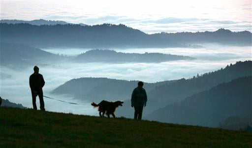 In this Nov. 13, 2005 file photo, a man and a woman walk a dog along the mountain Schauinsland near Freiburg, southern Germany, with fields of fog in the Rhine valley below.