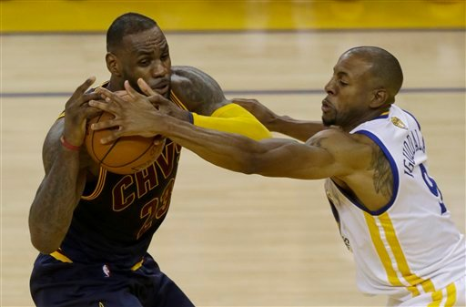 Golden State Warriors forward Andre Iguodala, right, reaches for the ball against Cleveland Cavaliers forward LeBron James during the first half of Game 1 of basketball's NBA Finals in Oakland, Calif., Thursday, June 2, 2016. (AP Photo/Ben Margot)