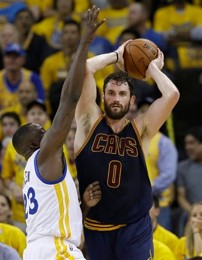 Cleveland Cavaliers forward Kevin Love (0) is guarded by Golden State Warriors forward Draymond Green during the first half of Game 1 of basketball's NBA Finals in Oakland, Calif., Thursday, June 2, 2016. (AP Photo/Marcio Jose Sanchez)