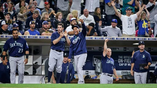 Seattle Mariners' Robinson Cano, left, and Leonys Martin celebrate during the Mariners' nine-run seventh inning against the San Diego Padres in a baseball game Thursday, June 2, 2016, in San Diego.. (AP Photo/Lenny Ignelzi)