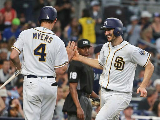 San Diego Padres' Adam Rosales slaps hands with Wil Myers while scoring in the Padres' seven-run fifth inning in a baseball game against the Seattle Mariners in a baseball game Thursday, June 2, 2016, in San Diego.. (AP Photo/Lenny Ignelzi)