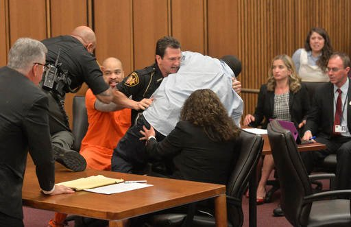 A court officer tackles the father of one of three victims of Ohio serial killer Michael Madison, left, who leaped over a table to attack the defendant June 2, 2016, in Cleveland. (AP Photo/David Richard)
