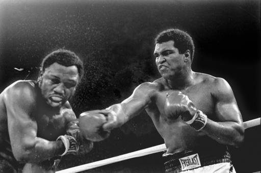 In this Oct. 1, 1975, file photo, spray flies from the head of challenger Joe Frazier as heavyweight champion Muhammad Ali connects with a right in the ninth round of their title fight in Manila, Philippines.